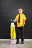 Ragazzo di scuola bello sveglio nel legame giallo della maglietta e cloase diritto casuale degli stivali alla moda al bordo nero  Immagine Stock