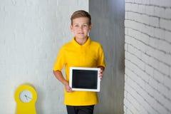 Ragazzo di scuola bello sveglio nel legame giallo della maglietta e cloase diritto casuale degli stivali alla moda al bordo nero  Fotografia Stock