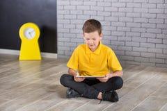 Ragazzo di scuola bello sveglio nel legame giallo della maglietta e cloase diritto casuale degli stivali alla moda al bordo nero  Immagine Stock Libera da Diritti