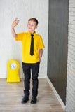Ragazzo di scuola bello sveglio nel legame giallo della maglietta e cloase diritto casuale degli stivali alla moda al bordo nero  Immagini Stock