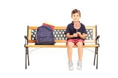 Ragazzo di scuola che si siede su un banco e che tiene una lecca-lecca della caramella Immagini Stock Libere da Diritti