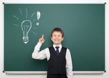 Ragazzo di scuola con la lampadina dipinta che ha idea Fotografie Stock Libere da Diritti