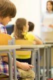 Ragazzo di scuola con lo smartphone sulla lezione all'aula Immagine Stock Libera da Diritti