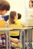 Ragazzo di scuola con lo smartphone sulla lezione all'aula Fotografia Stock