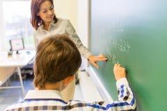 Ragazzo di scuola con scrittura dell'insegnante sul bordo di gesso Immagine Stock