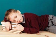Ragazzo di scuola stanco addormentato sui libri piccolo studente che dorme sul tex Fotografia Stock Libera da Diritti