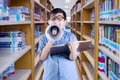Ragazzo di scuola sveglio con il megafono nella biblioteca Fotografie Stock