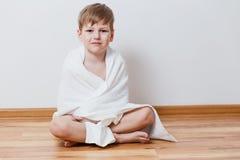 Ragazzo di sei anni sveglio che si siede sul pavimento su fondo bianco fotografie stock libere da diritti