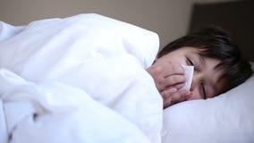 Ragazzo di starnuto malato a letto stock footage