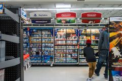 Ragazzo di Wal-Mart Video Game Section Little che esamina compera dei giochi Fotografia Stock