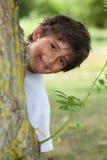 Ragazzo dietro il tronco di albero immagini stock