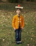 Ragazzo divertente con il libro sulla sua testa Fotografia Stock