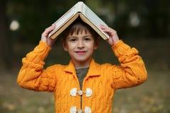 Ragazzo divertente con il libro sulla sua testa Fotografia Stock Libera da Diritti