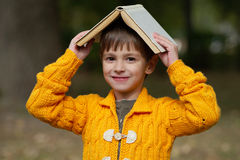 Ragazzo divertente con il libro sulla sua testa Fotografie Stock Libere da Diritti