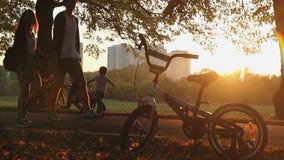 Ragazzo divertente del bambino che impara ciclare, molta gente che ha resto in parco al tramonto video d archivio