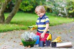 Ragazzo divertente del bambino che pianta i fiori in giardino su sprinig Fotografia Stock Libera da Diritti