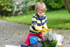 Ragazzo divertente del bambino che pianta i fiori in giardino su sprinig Fotografie Stock
