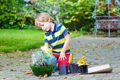 Ragazzo divertente del bambino che pianta i fiori in giardino su sprinig Immagine Stock