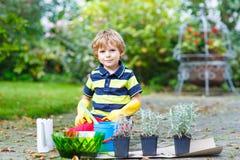 Ragazzo divertente del bambino che pianta i fiori in giardino su sprinig Fotografia Stock