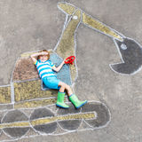 Ragazzo divertente del bambino con l'immagine del gesso dell'escavatore Fotografie Stock