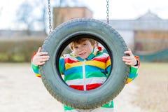 Ragazzo divertente del bambino divertendosi con l'oscillazione a catena sul campo da giuoco all'aperto Fotografie Stock Libere da Diritti