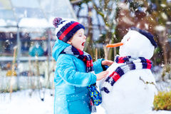 Ragazzo divertente del bambino in vestiti variopinti che fanno un pupazzo di neve, all'aperto Fotografia Stock