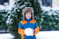 Ragazzo divertente del bambino in vestiti variopinti che giocano all'aperto durante le precipitazioni nevose Svago attivo con i b immagini stock