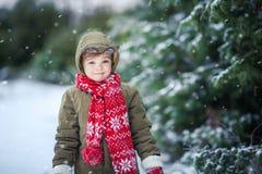 Ragazzo divertente del bambino in vestiti variopinti che giocano all'aperto durante le precipitazioni nevose Svago attivo con i b immagine stock