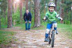 Ragazzo divertente felice del bambino in impermeabile variopinto che guida il suo primo Immagini Stock