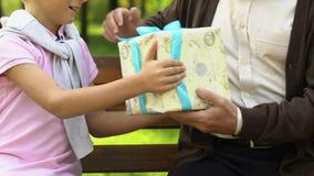 Ragazzo dolce che dà regalo di Natale a suo nonno anziano, festa in famiglia stock footage