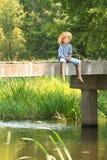 Ragazzo durante la pesca con l'amo con la barretta sul ponte Fotografie Stock Libere da Diritti