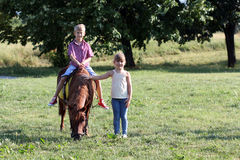 Ragazzo e bambina con il cavallo del cavallino Immagine Stock Libera da Diritti