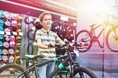 Ragazzo e bicicletta nel negozio di sport fotografia stock