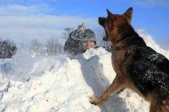 Ragazzo e cane che giocano nella neve Immagine Stock