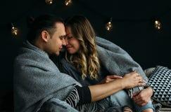 Ragazzo e girfriend che si toccano che si siede sul letto con le coperte ed i cuscini grigi Stanza accogliente con le luci Fotografie Stock Libere da Diritti