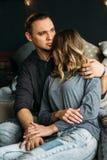 Ragazzo e girfriend che si toccano che si siede sul letto Stanza accogliente con il concetto romantico e di amore delle luci, Uom Immagini Stock