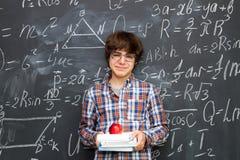Ragazzo e lavagna riempiti di formule di per la matematica Fotografia Stock