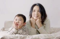 Ragazzo e madre che guardano insieme TV Fotografia Stock