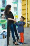 Ragazzo e mamma alla città, al fiore ed al presente Concetto di celebrazione di giorno di madri Fotografia Stock Libera da Diritti