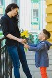 Ragazzo e mamma alla città, al fiore ed al presente Concetto di celebrazione di giorno di madri Fotografie Stock Libere da Diritti