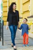 Ragazzo e mamma alla città, al fiore ed al presente Concetto di celebrazione di giorno di madri Fotografia Stock