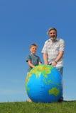 Ragazzo e nonno che si levano in piedi globo vicino Fotografie Stock