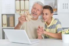 Ragazzo e nonno con un computer portatile e un modello dell'aereo Immagine Stock Libera da Diritti