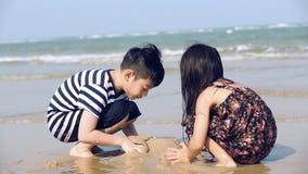 ragazzo e ragazza ฤsian duro sul lavoro, castelli di costruzione nella spiaggia di sabbia stock footage