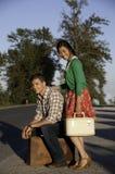 Ragazzo e ragazza al bordo della strada con la valigia Immagine Stock