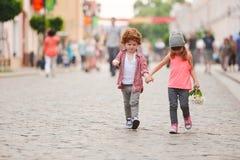 Ragazzo e ragazza che camminano sulla via immagini stock libere da diritti