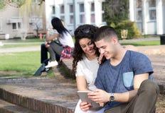 Ragazzo e ragazza che esaminano compressa Immagine Stock Libera da Diritti