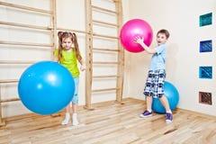 Ragazzo e ragazza che giocano con le sfere Fotografia Stock