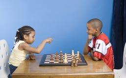 Ragazzo e ragazza che giocano scacchi Fotografia Stock Libera da Diritti