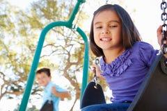 Ragazzo e ragazza che giocano sull'oscillazione in parco Immagine Stock Libera da Diritti